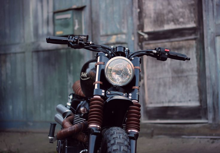 Triumph Scrambler by BAAK, with leather fork gaiters and Bates headlight.