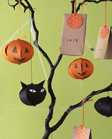 Scare up fun at a Halloween party with a centerpiece that displays favor bags and seasonal ornaments. Branches hold evil-eyed black cats and jolly jack-'o-lanterns fashioned from paper, as well as candy-filled bags for guests to bring back to their lairs.