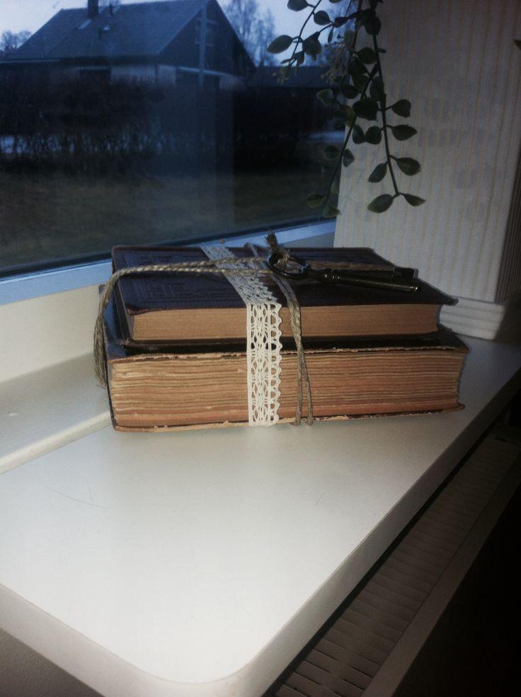 Böcker från loppis ihopbundna med naturtråd och spetsband, fastbunden nyckel ovanpå.