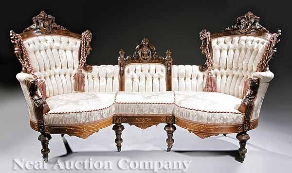 American Renaissance Carved And Gilt-Incised Walnut Parlor Suite Attributed To John Jelliff, Newark, N.J., Comprising Of A Sofa And Two Side Chairs, The Sofa With A Tripartite Back, All Crested With Carved Busts Of Crowned And Bejeweled Women, Foliate Cartouches, And With Pendant Drops, Padded Arms Terminating In Busts, Scalloped And Incised Seat Rails, Turned Legs With Casters, All Finely Upholstered In Tufted Fabric   c.1870  -  Liveauctioneers