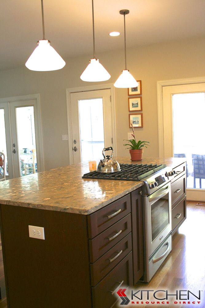 a kitchen island with shaker cabinets in a cherry java finish