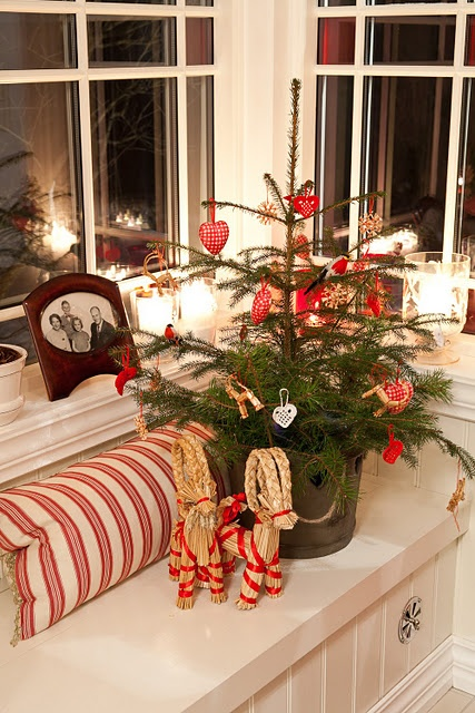 that xmas tree, the striped pillow, those beautiful glowing candles. so charming!