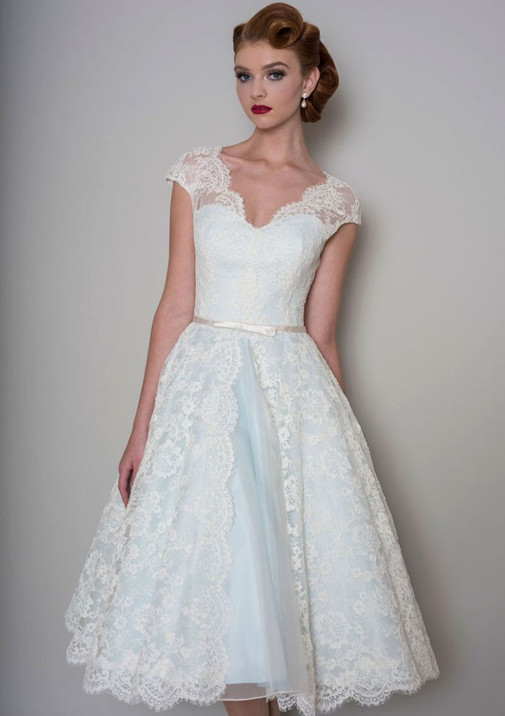 Cute a-line tea length bridal gown with cap sleeves ivory corded lace overlay on the pale blue skirt, trimmed with a narrow satin bow belt.