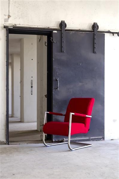 On adore l'imposante porte coulissante en métal façon usine, et la manière dont le fauteuil Angelica rouge ressort dans ce décor industriel.