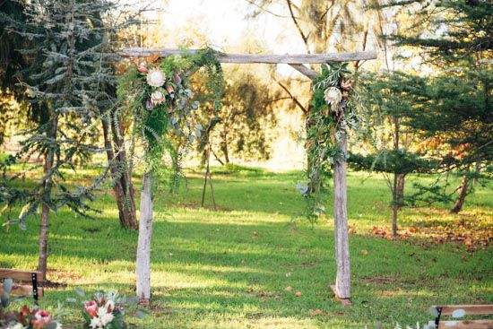 timber arbour / perth wedding / australian native floral arrangement / outdoor ceremony / core cider house / winter wedding / rustic glamour styling  Rustic Winter Orchard Wedding Inspiration featured on Polka Dot Bride captured by Earthbound Images http://www.earthboundimages.com.au