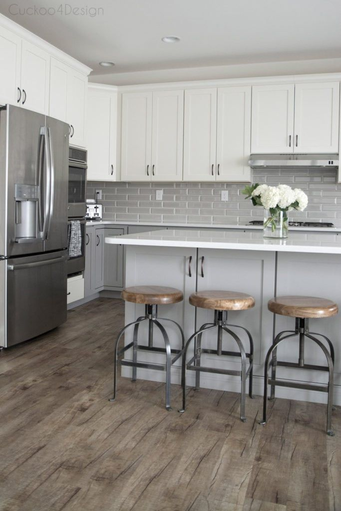 Vinyl Plank Flooring And Wood And Metal Counter Stools In Grey And White Kitchen White Kitchen Design Gray And White Kitchen Grey Wood Floors Kitchen