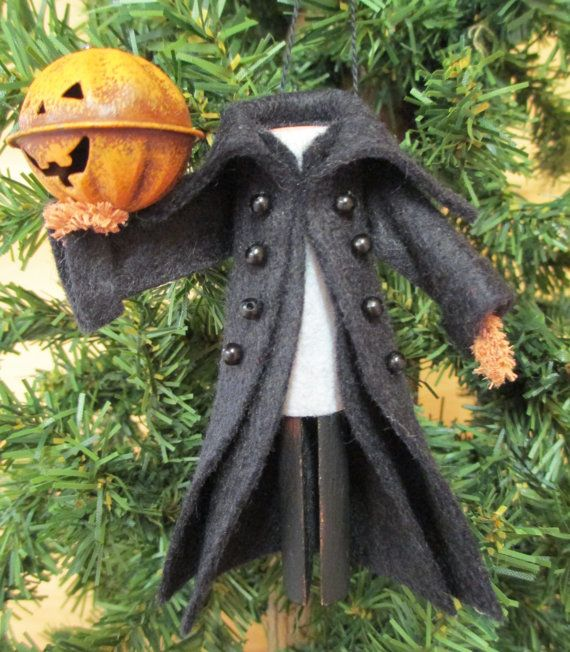 "ModerationCorner- on Etsy. Originally introduced in 2012, we've updated our headless horseman ornament with a more detailed coat and jack-o-lantern head. He is created from a clothespin, wood ball, pipe cleaner and scraps of wool felt. A loop of heavy black embroidery thread serves as the hanger. Approx. dimensions: 4.5"" H x 3.5"" W"