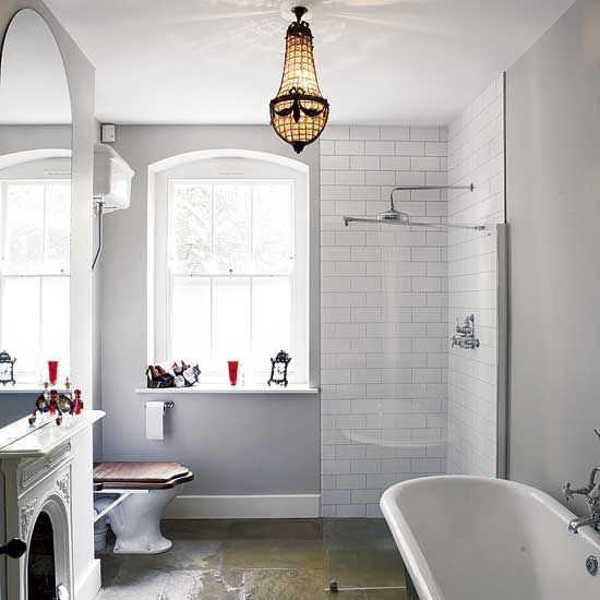 This bathroom highlights how a mix of materials and details can work together – an ornate chandelier set against a backdrop of utility tiles, period fittings and a contemporary glass screen.