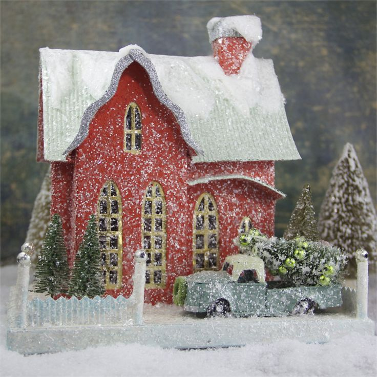 Red putz house with pickup truck carrying a Christmas tree.
