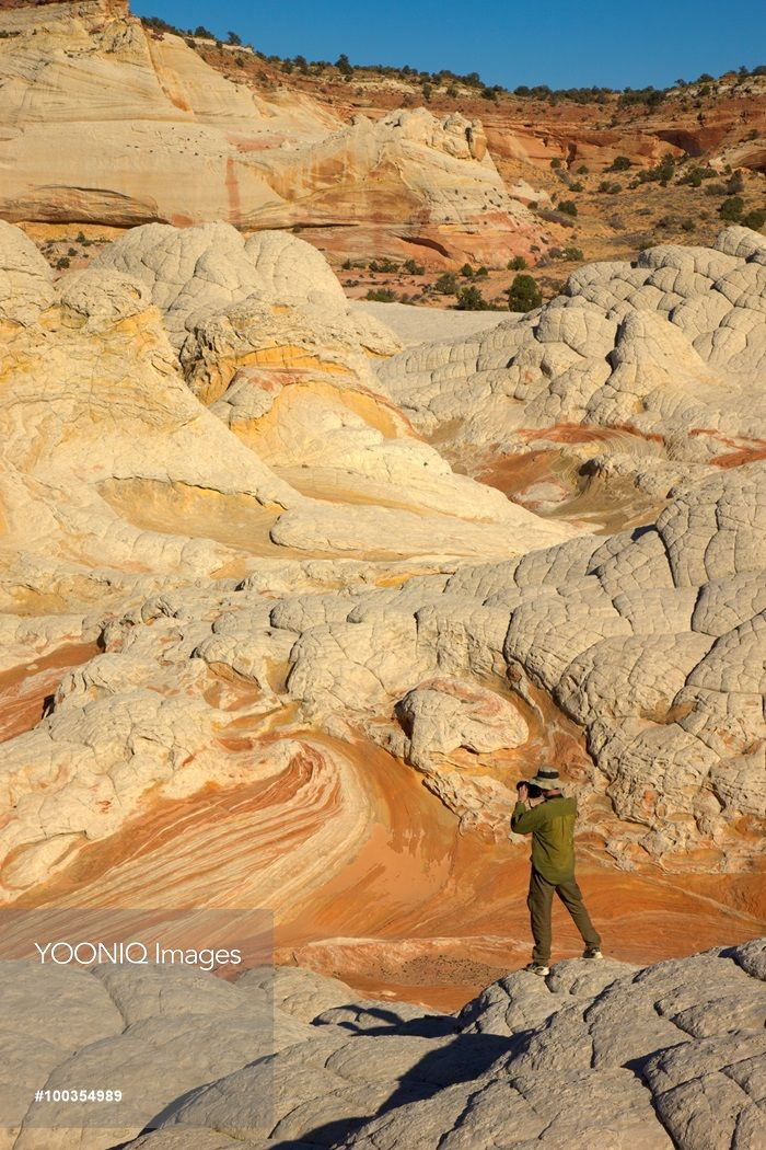 Yooniq images - Hiker photographing Colorado Plateau sandstone formations.