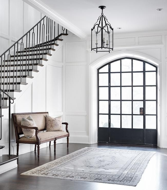 Elegant foyer features floor to ceiling wainscoting lined with a French settee alongside a gray ...