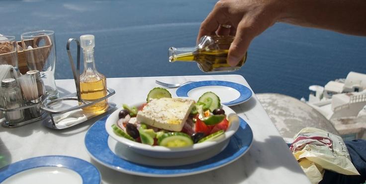 A Greek man putting Greek olive oil in a Greek salad