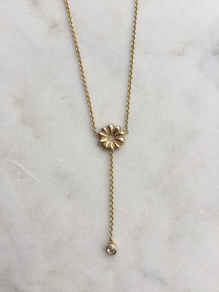 A whimsical version of our signature Aster Ray, with a rose cut diamond dangling through your heart centre. Luxuriously graceful, for the gorgeous goddess in us all.   - Solid 14 karat yellow gold Aster Ray, 1mm diameter  - 14 Karat yellow gold chain, 18 inches - Rosecut diamond, 2.5 mm
