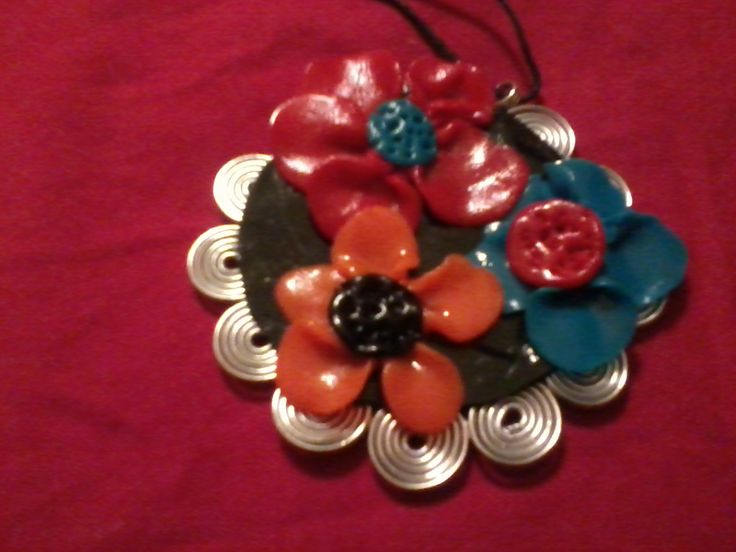 Clay pendant with colored flowers wrapped with wire spirals