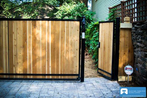 Wooden front sliding gate with pedestrian side entry the for Wooden sliding driveway gates