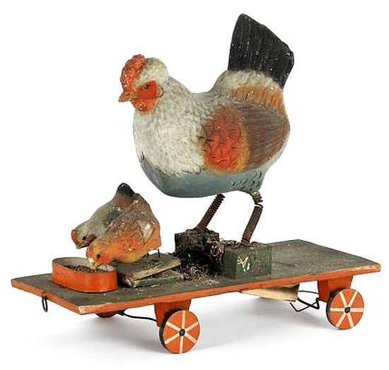 Highly unusual German squeak toy on wheels, late 19th c., with a mother and two chicks feeding,