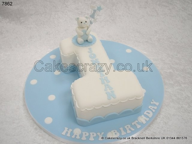 Number one shaped 1st birthday cake in white on a baby blue iced polka dot board and trimmings. Modelled sugar teddy holding a number 1 wired topper