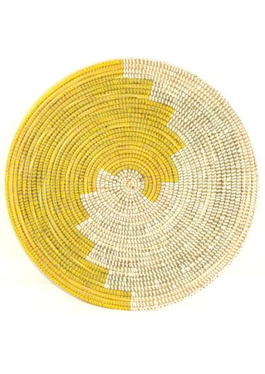 "Great idea for mat time.  Geometric Sun Oversize Trivet                            Crafted by local women living in the West African nation of Senegal, this trivet is constructed using local 'njodax' grass and plastic often recycled from rugs and prayer mats.    Millet grass and plastic. 16"" diameter."