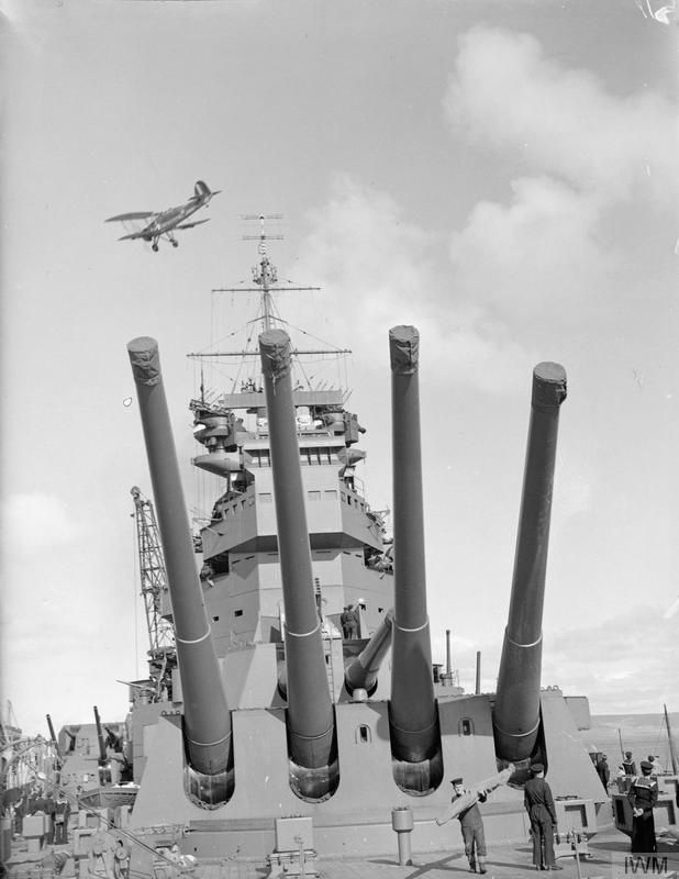 Brand new 14 in King George V class battleship HMS Prince of Wales with Fairey Swordfish torpedo bomber overhead, April 1941.  Both were to play a part in the Bismarck saga the following month.  Prince of Wales was sunk by Japanese aircraft that December.