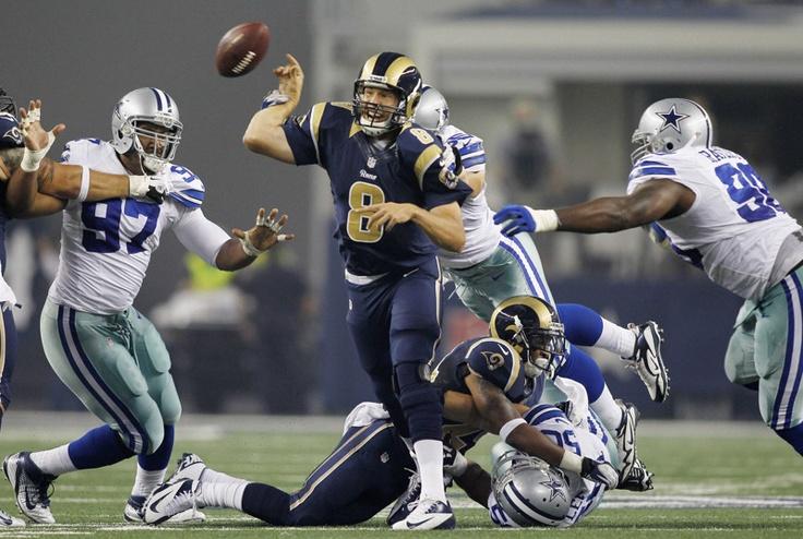 El mariscal de campo de los St. Louis Rams, Sam Bradford (8) es golpeado por el apoyador de los Dallas Cowboys, Albright Alex mientras el ala defensiva Jason Hatcher (izq.) y el tacleador defensivo Jay Ratliff (der.) ejercen presión en un partido de fútbol americano de la NFL en Arlington, Texas el 25 agosto de 2012. | Créditos: REUTERS / Mike Stone