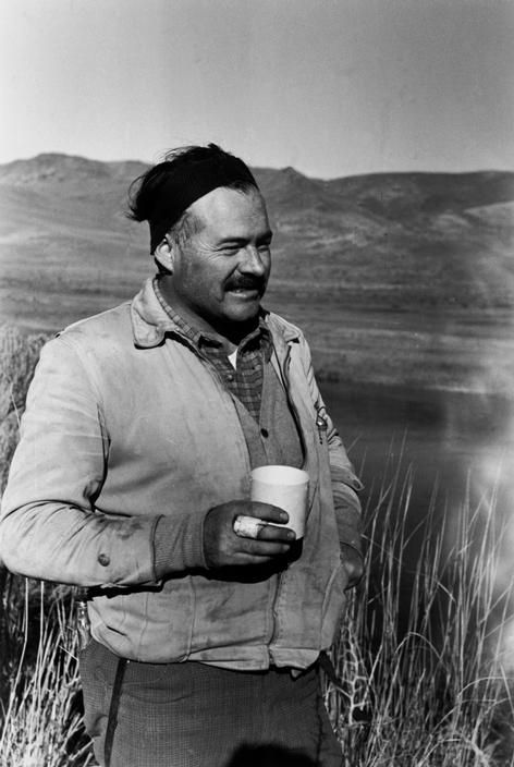 USA. Ernest Hemingway taking a break during a duck hunting trip. By Robert Capa, (1940)