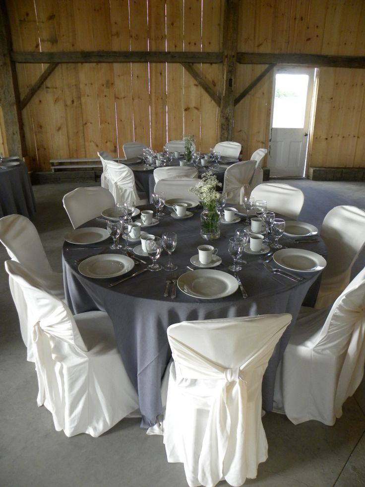 round table with light grey raw silk cover and ivory criss cross chair covers
