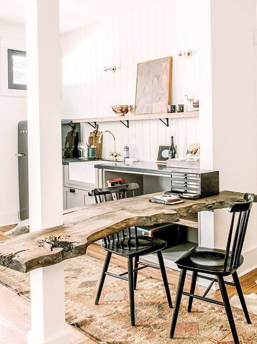 Real wood multi purpose table and white wall paneling in a modern styled kitchen.