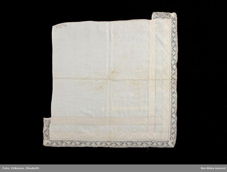 Halskläde av vitt linne. Fyrkantig duk med broderat mönster, 'krus' i vitt lingarn.