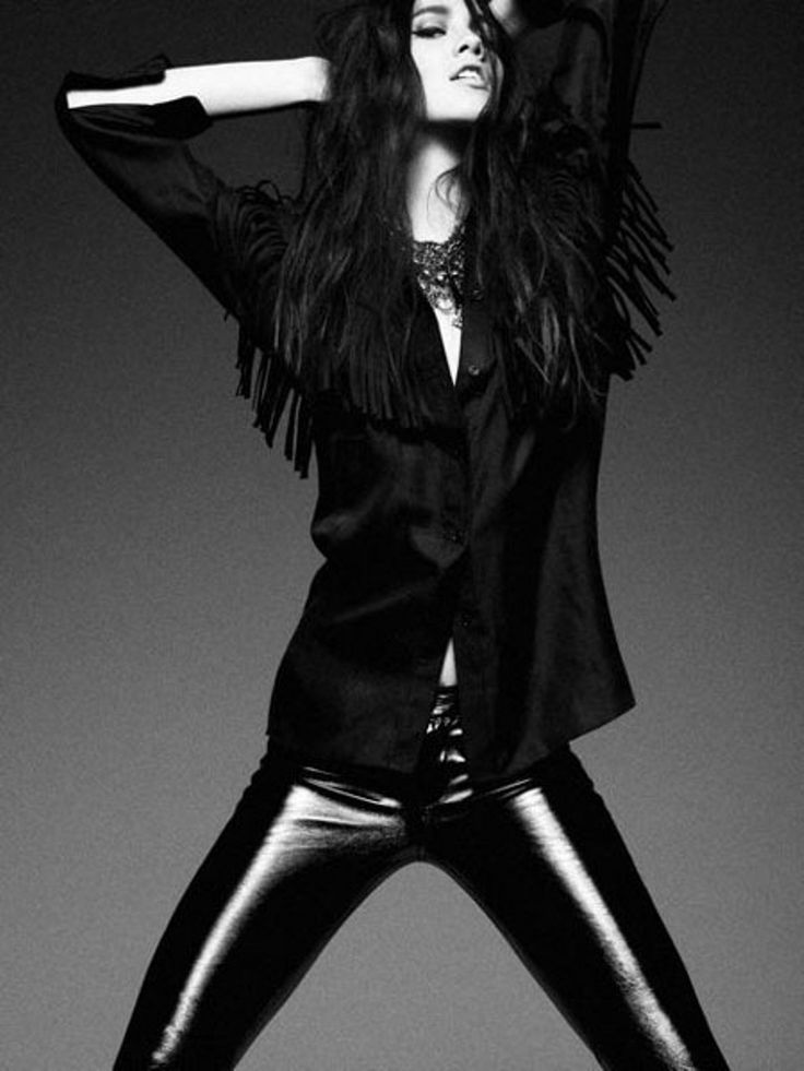 Black and white photo of model in shiny vinyl jeans.