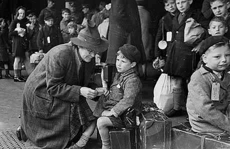 A helper at Paddington Station in London fixing a label onto a child being evacuated from London during the war.