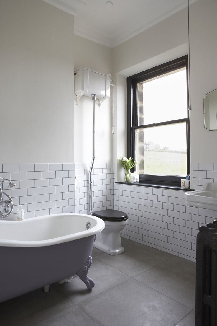 House bathroom. Metro tiles, black painted window, art deco mirror, roll top bath.