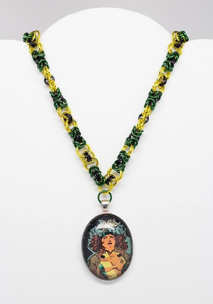 This one of a kind, handmade necklace is 22 inches long and is made up of a mix of yellow, black, and green rings as inspiration from the X-Men character Rogue.  Attached is a glass oval  pendant measuring 40x30mm with a photo of Rogue recycled from X-Men comic #1 (1991).  You can find it at www.CarolineCospay.Storenvy.com  #necklace #jewelry #marvelcomics #marvel #Rogue #Xmen