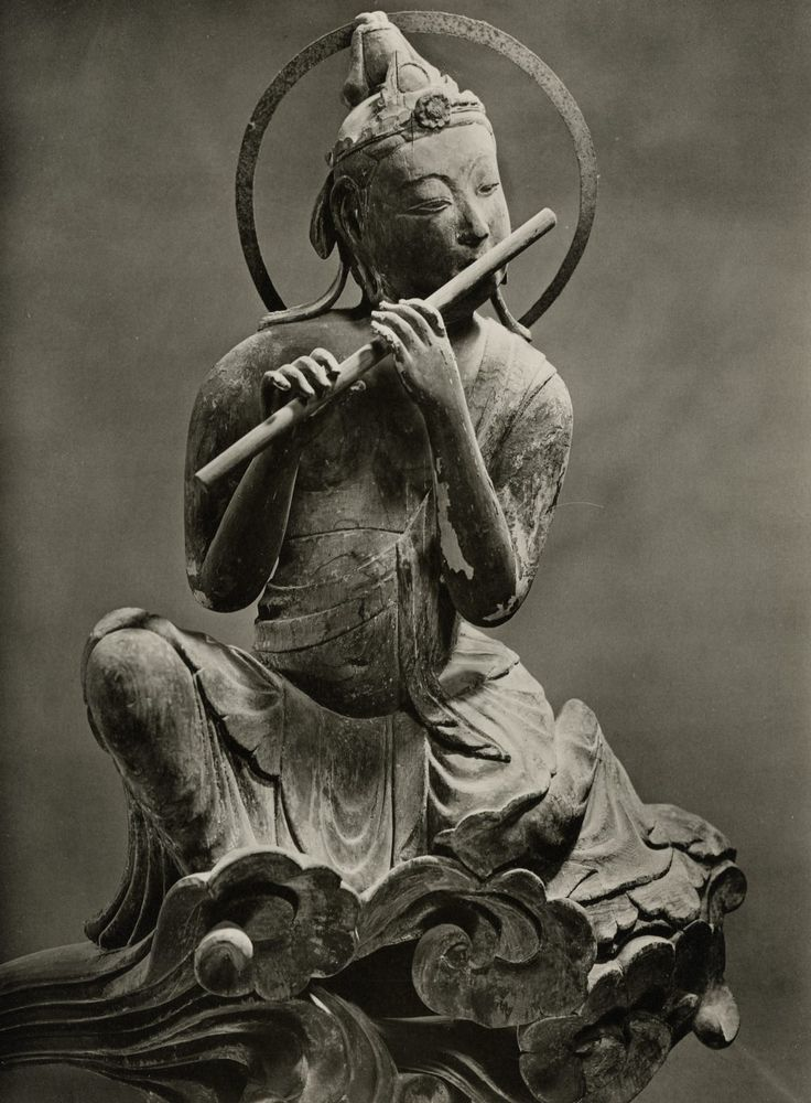 Bodhisattva on a cloud playing a Flute. 1053 AD carved wood. Byodo-in Temple. Japan.