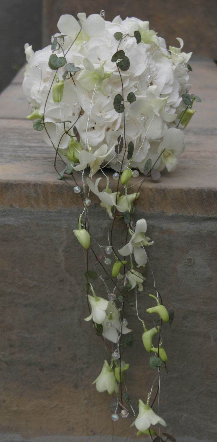 Modern bridal bouquet of white Hydrangeas and orchids with trails of crystals and Ceropegia 'string of hearts'