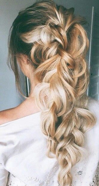 Creating this bulked up ponytail is easier than it looks. Start by putting hair into a ponytail and separating it into two sections. Begin a braid in each section and when you are about one third the way down, combine the braids into one. Expand the braids heavily, so that each loop is defined and sprinkle with Big Sexy Hair Powder Play for texture and grip. https://www.sexyhair.com/products/powder-play-volumizing-texturizing-powder.html