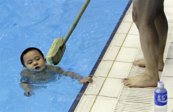 A coach holding a broom tries to prevent a boy from holding onto the edge of the pool as he learns swimming during a diving training session at a training center in Beijing July 27, 2011.  REUTERS/Jason Lee