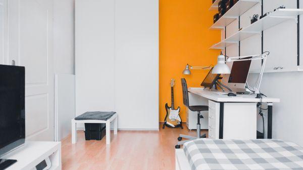 Houd een kleine slaapkamer licht van kleur en geef 1 muur een accent kleur! #slaapkamer #oranje #licht #bed