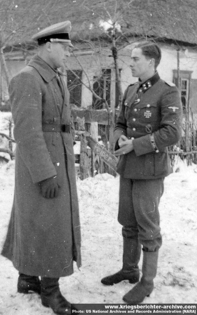 War criminal the butcher of Malmedy (1944) - SS-Standartenführer Joachim Peiper (right), serving with SS-Division Leibstandarte SS Adolf Hitler on the Eastern Front, is photographed in conversation with another officer probably in 1943. Peiper, adjutant to Heinrich Himmler between 1940 and 1941, was Himmler's protege and one of the most aggressive young panzer commanders of WW2. He survived the war and was killed by Nazi hunters in France in 1976.