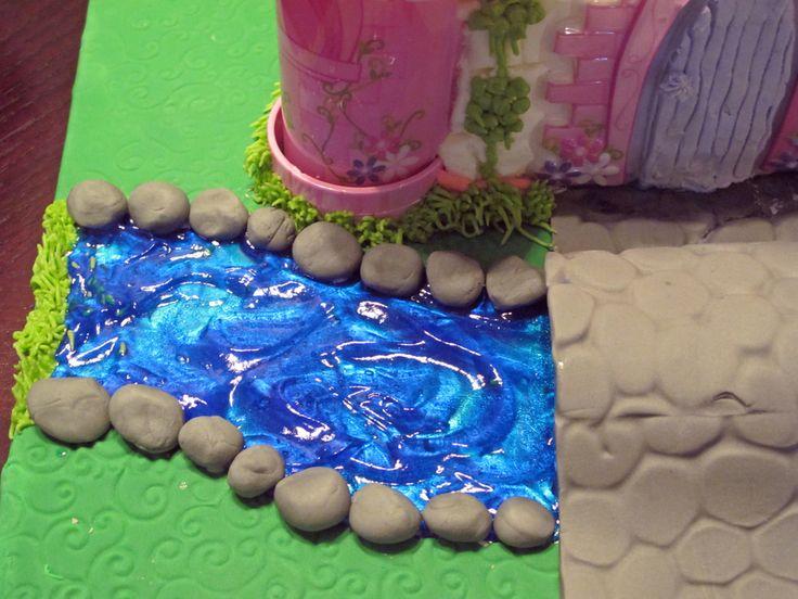 Disney Princess Cake Disney princess castle cake with princess carriage, cobblestone path and bridge, and moat.