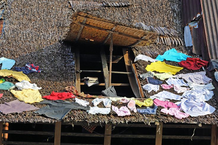Drying laundry on the thatched roof of a traditional house in south nias. Nias Island, Indonesia. Photo by Bjorn Svensson. www.visitniasisland.com