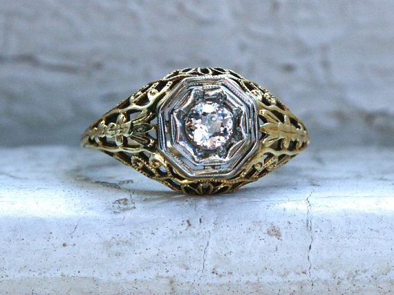 This Fabulous Vintage Filigree Diamond Engagement Ring is just gorgeous! Crafted in 14K Yellow Gold, this ring features amazingly detailed openwork filigree with beaded edges, hand engraving, and a unique octagon Illusion Head done White Gold. In the center, the ring holds One Old Mine Cut Diamond, approximately 0.25ct in weight, of I/SI2 quality. Truly a fabulous ring and a rare find! Other Important Details: The ring is a Size 6. The ring is stamped 14K, and had been tested to be 14K Y...