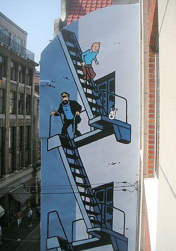 """*Mur BD Tintin - Bruxelles Pentagone La fresque de Tintin d'après le héros de Hergé fut inaugurée le 20 juillet 2005, et aurait du être la toute dernière de la série, mais rien n'était moins vrai... Sa superficie est d'environ 35 m². Elle se trouve qu'à une bonne dizaine de mètres de cet autre Bruxellois célèbre, Manneken-Pis. Réalisation de G. Oreopoulos et D. Vandegeerde de la société """"Art Mural""""."""