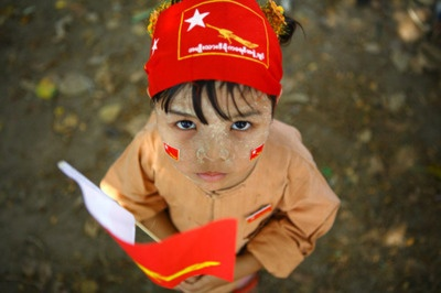 Yangon, Myanmar. A child holds stickers and party flag for Aung San Suu Kyi's National League for Democracy party.