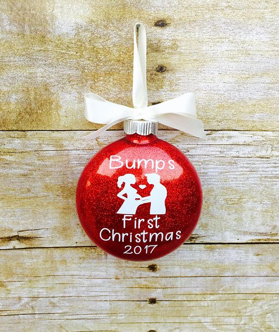 Bumps first Christmas ornament. Celebrate your baby bump this Christmas! A fun memory of your baby bumps first Christmas or a fun way to announce your pregnancy to family and friends. Pregnancy keepsake This listing is for 1 glass glittered Christmas ornament. Ornament measures 4. Choose your choice of glitter color for ornament from the drop down. The design is done in white permanent vinyl unless otherwise requested! ****ADDITIONAL SHIPPING INFORMATION**** -Item will be generally be sh...