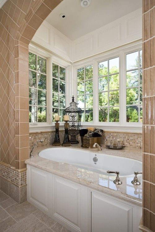 bathtub nook with great windows, like the staging of items around the tub