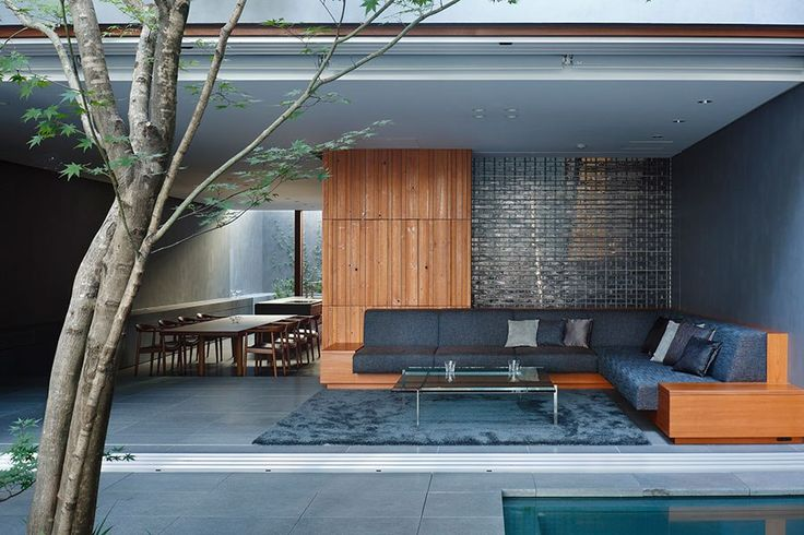 A retractable curtain of lightweight metal demarcates the courtyard from several living spaces, including the dining and sitting rooms, seen here.