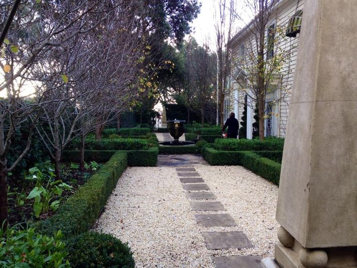 Wide gravel path with inlays and boxwood perimeter