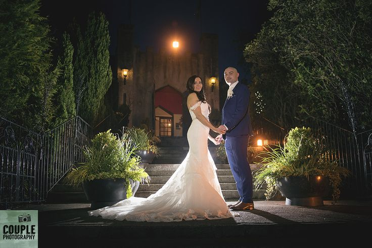 Colourful night time photo of the bride & groom outside Cabra. Weddings at Cabra Castle photographed by Couple Photography.