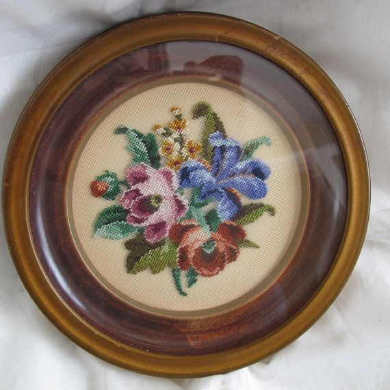 Gorgeous floral petit point picture featuring a bouquet of blue iris, violets and I believe peony. Round wood frame with glass that is offset from the needlework. Overall diameter is 7 inches. Frame is about 1 inch deep. Needlework is about 4 1/4 inches in diameter. Original frame,