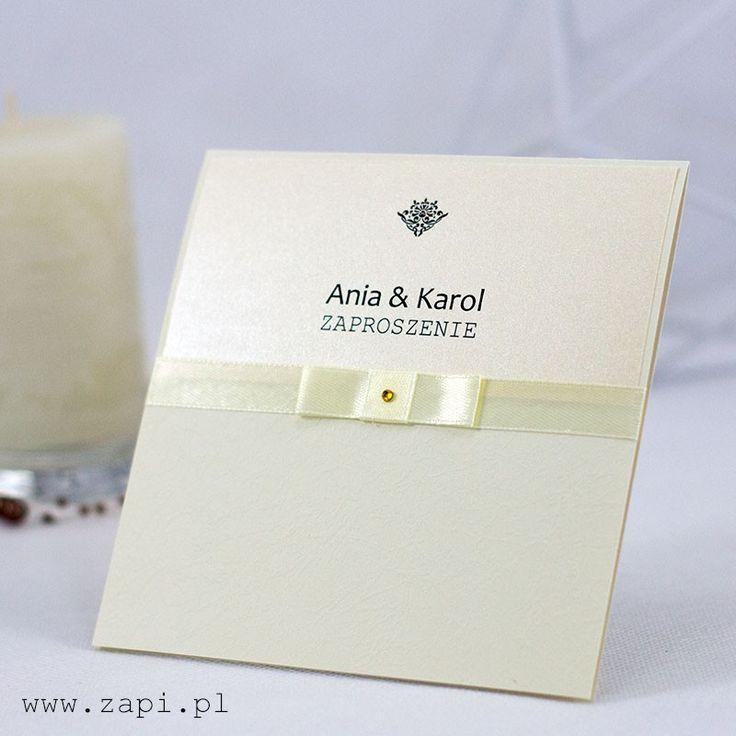 Kremowe zaproszenie ślubne z tasiemką i złotą aplikacją. Kartka wykonana jest na eleganckim papierze dekoracyjnym z tłoczeniami.